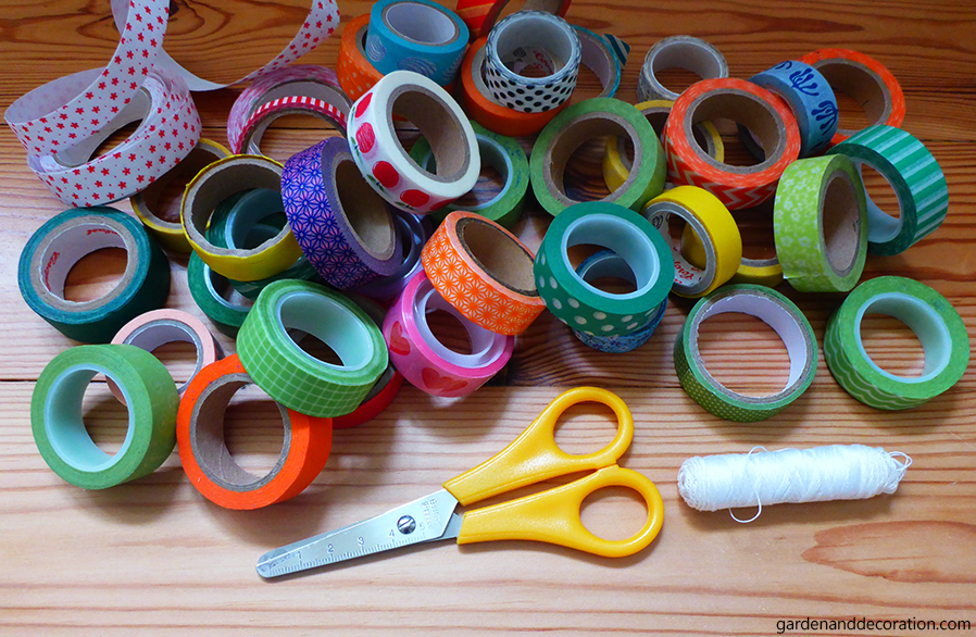 Washi tapes, pair of scissors and white thread on floor