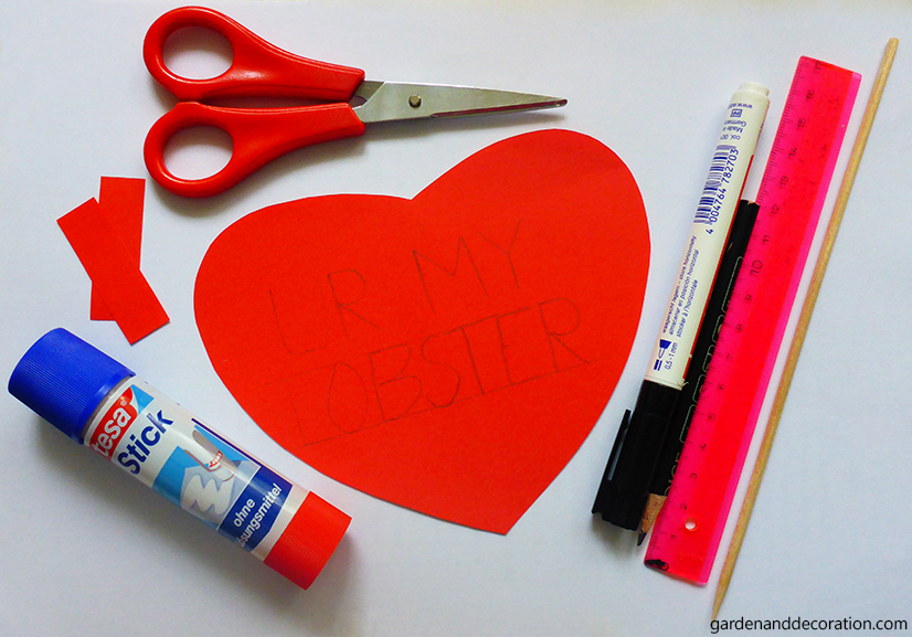 Scissors, red heart,glue, stick, marker and ruler on a table.